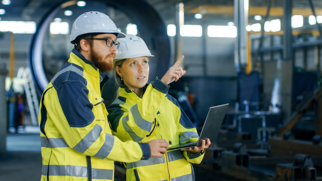 Portrait of male and female packaging engineers in hard hats and safety jackets; woman is pointing at something in the warehouse while both look in that direction