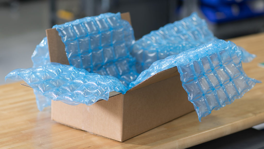 Pregis Inspyre HC Protective Packaging in water-blue color draped inside an open cardboard box