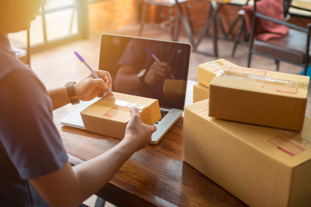 E-commerce seller packaging products in boxes to be shipped to customers