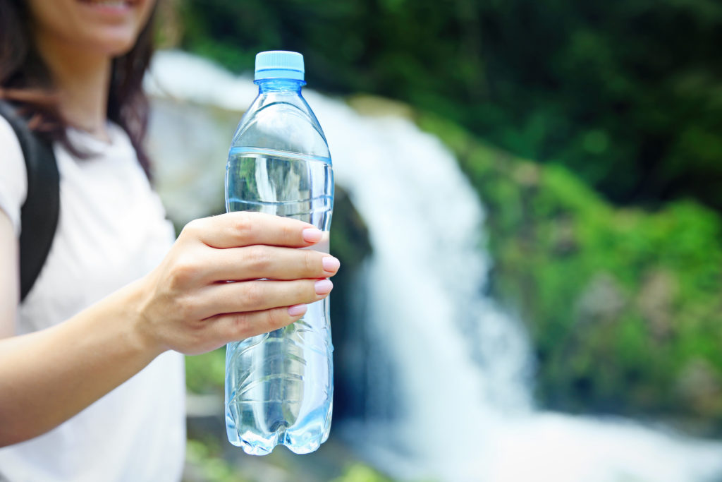 Woman holding a plastic bottle of water, standing in front of a waterfall