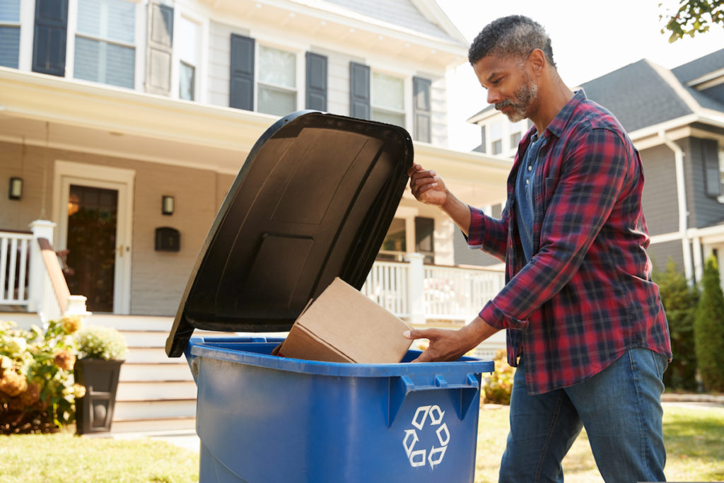 Man Filling Recycling Bin in front of his house