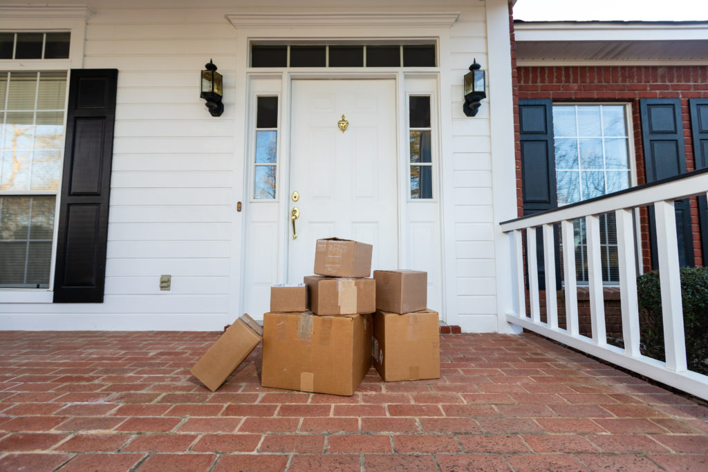 pile of boxes from online shopping in front of someone's front door