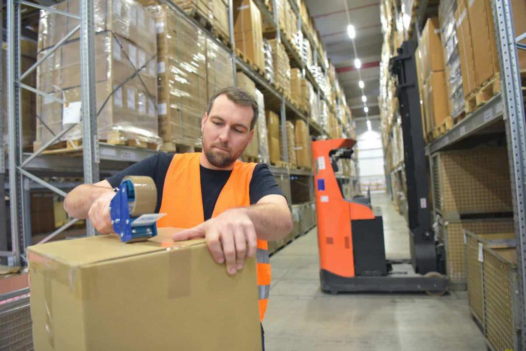 Man taping a cardboard box closed
