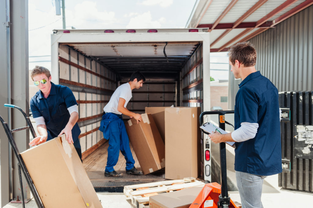 Men loading a delivery truck with large packages